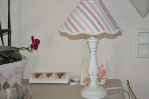 Pied de lampe en bois, surmonté d'un abat-jour de diamètre 7 cm. Recouvert de tissus et terminé par une bordure blanche à pompons