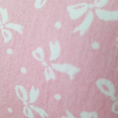 Motif du tissu rose imprimé de petits nœuds blancs