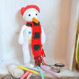 Bonhomme de neige emmitouflé dans son écharpe et dans son bonnet. Création fait-main