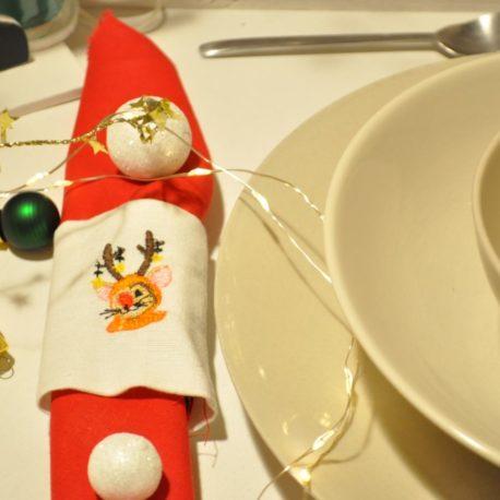 Gros plan. Suggestion de présentation. Broderie petite souris renne de Noël sur rond de serviette en tissu. Création artisanale Bébé Boutchou