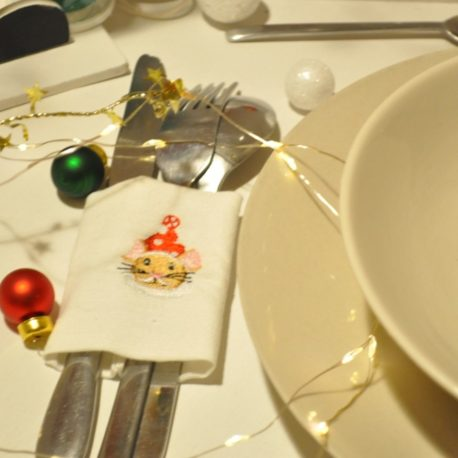 Suggestion en gros plan de présentation. Broderie petite souris de Noël sur rond de serviette en tissu pour couverts. Création artisanale Bébé Boutchou